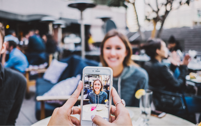 An iPhone photographer frames is subject on the screen.