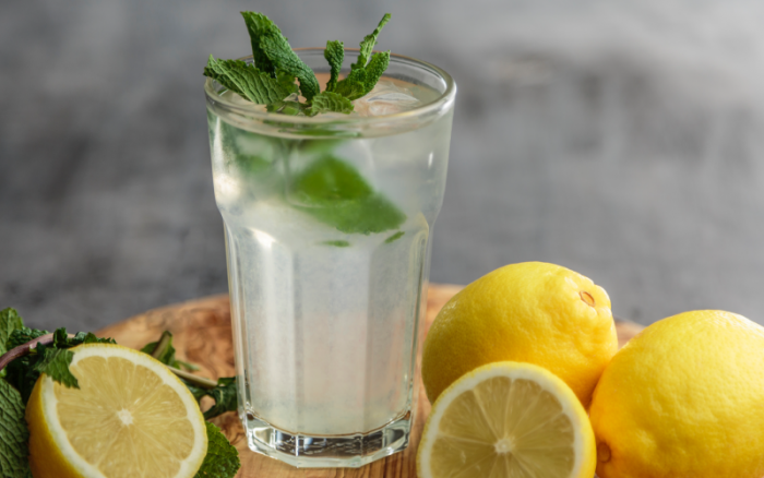 A lemon and mint beverage in a glass.